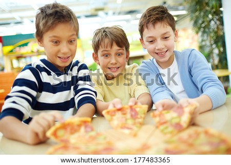 Three boys sitting thrilled with pizza