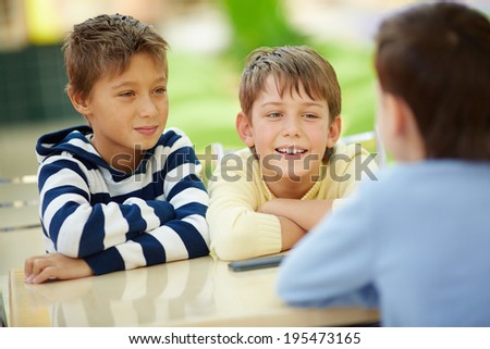 Three boys spending time in cafe - stock photo