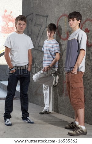 Three boys standing beside a wall - stock photo