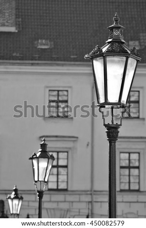 Three brass antique street lamps in a row in black and white - stock photo