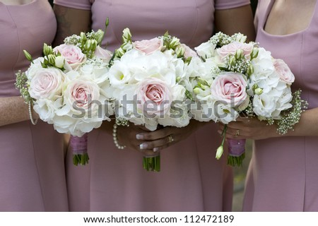three bridesmaids in pink dresses holding wedding bouquets of white roses - stock photo