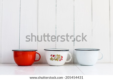 Three bright colorful enameled mugs on white painted wooden table, rustic kitchenware and decor, vintage kitchen background - stock photo