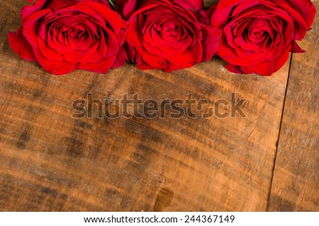 Three bright red roses on a wooden table - stock photo