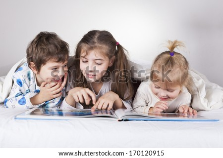Three brothers boy and two girls lying in bed with a book