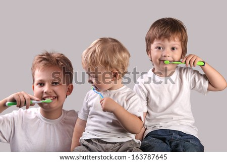 three brothers brushing teeth together - stock photo
