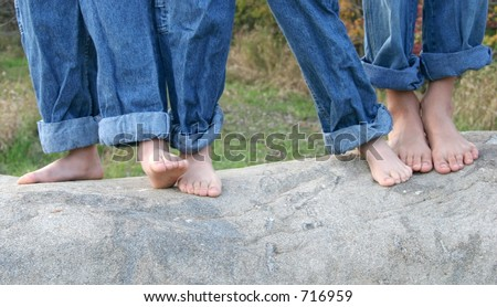 Three brothers dancing barefoot on rock. - stock photo
