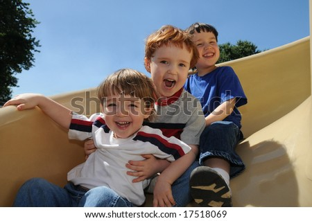Three brothers have a great time sliding down a spiral slide on a neighborhood schoolyard - stock photo