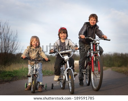 three brothers ride bikes - stock photo
