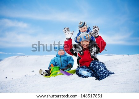 Three brothers sitting on the snow and playing together on winter day