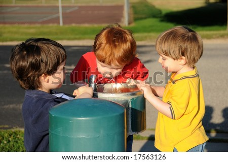 Three brothers take turns drinking water from a drinking fountain at a neighborhood park. - stock photo