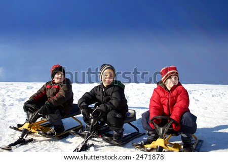 Three brothers  Tobogganing on a nice winter day - stock photo