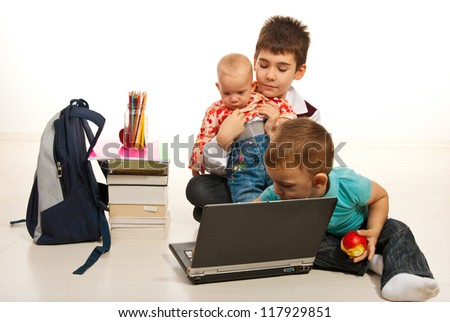 Three  brothers using laptop and  sitting together on floor home - stock photo