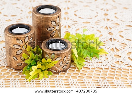 Three brown ancient style candle nests and green leaves on cloth background. - stock photo