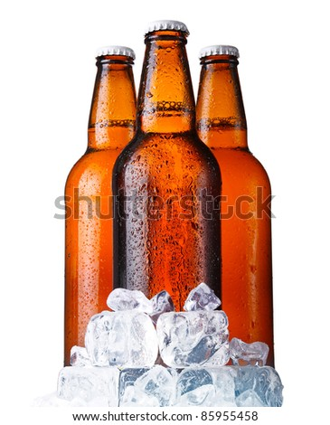 Three brown bottles of beer with ice isolated on white background - stock photo