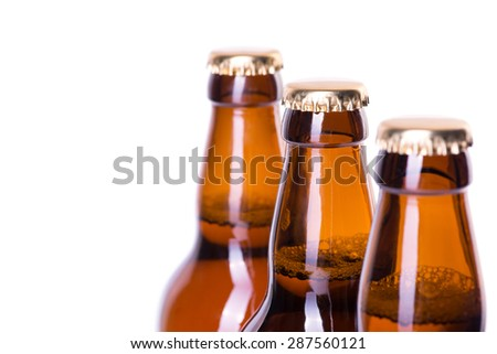 Three brown bottles of ice cold beer isolated on white - stock photo