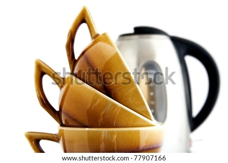 Three brown cups and kettle on a white background - stock photo