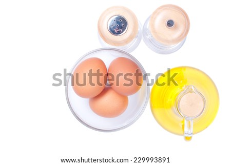 Three brown eggs in a glass bowl close spices on white isolated background top view - stock photo
