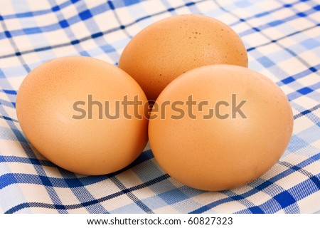 Three brown hen's eggs on the blue chequered cloth