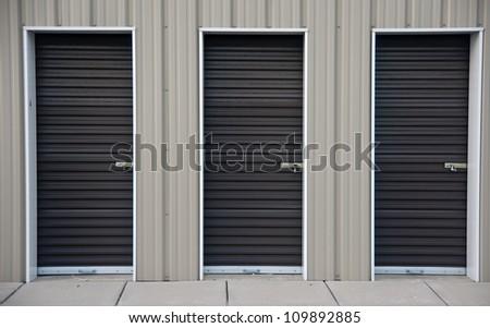 Three brown metal doors of an outdoor storage unit - stock photo