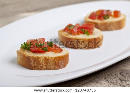 Three Bruschetta with tomatoes and basil leaves arranged in a platter - stock photo