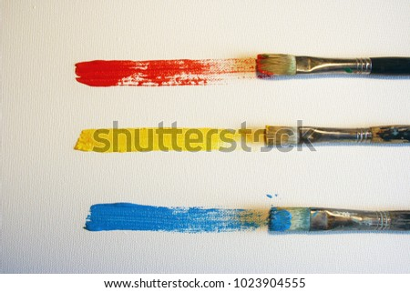 Three brushes and three colors on canvas