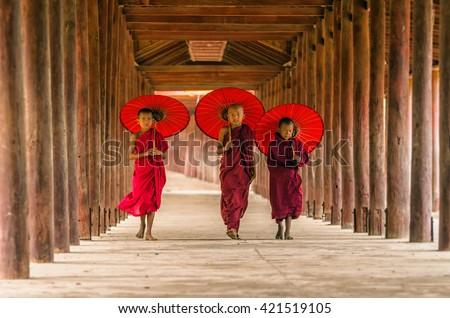 Three Buddhist novice are walking in pagoda,myanmar - stock photo