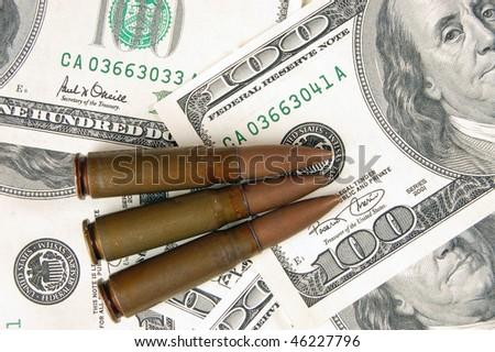 Three bullets on dollars background - stock photo