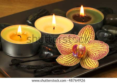 Three burning candles and orchid flower with vanilla pods. Aromatic spa treatment - stock photo