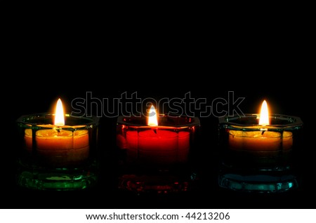 Three burning candles form a bottom border on black, with copy space. - stock photo