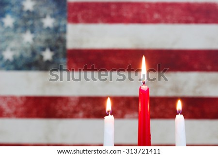 Three burning candles in front of blurred background of vintage American flag on canvas - stock photo