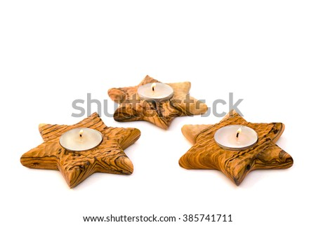 Three burning candles in of wooden candlesticks (star of David) on white background.  - stock photo