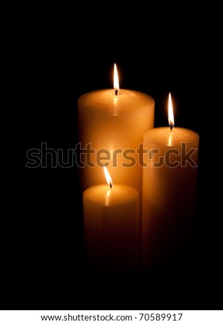 Three burning candles of differing size on a black background - stock photo