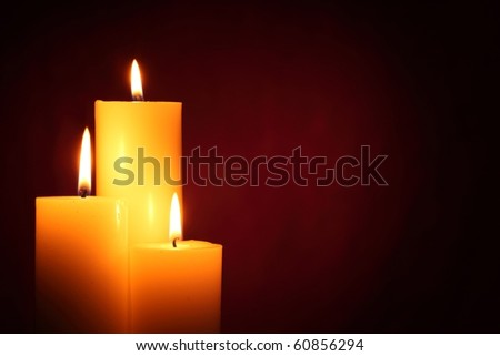 Three burning candles on red background - stock photo