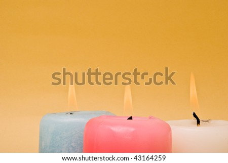 Three burning candles over a yellow background - stock photo