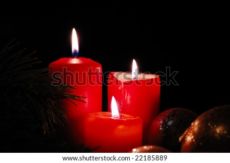 Three burning candles with seasonal decorations. Low key lighting.