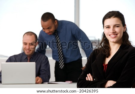 three business associates with a grey laptop