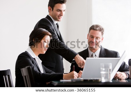 Three business associates working together, with one associate pointing at laptop - stock photo