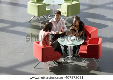 Three business colleagues having a meeting over a hot drink in an office building - stock photo