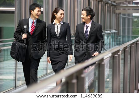 Three Business Colleagues Having Discussion Whilst Walking Outside Office - stock photo