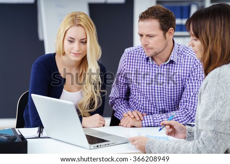 Three business colleagues in a meeting sitting grouped around a laptop computer reading information on the screen - stock photo