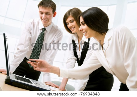 Three business colleagues standing around table and working together, looking at monitor, smiling - stock photo