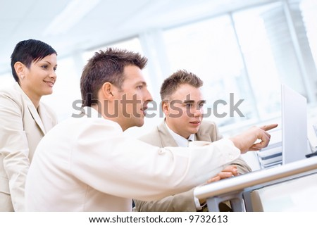 Three business colleagues using laptop computer in office, pointing, smiling. - stock photo