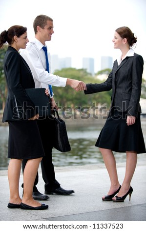 Three business executives meeting and greeting by a river in the City