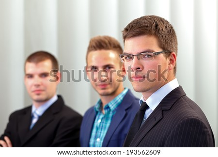 Three business men in their office after a successful deal