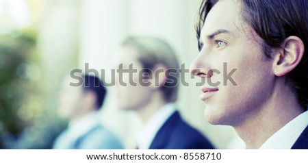 three business men standing and looking in same direction - stock photo