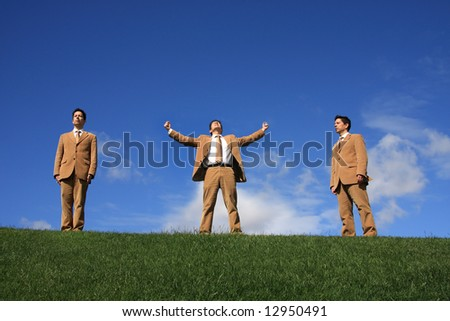 Three business men with different posture at the top of a hill - stock photo
