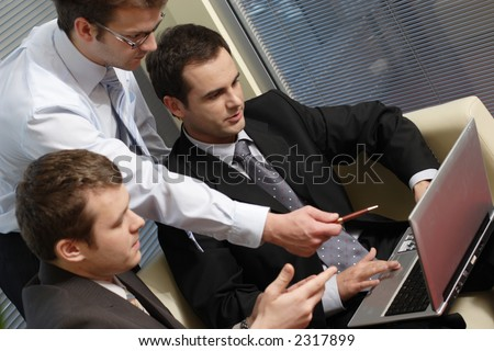 Three business men working together on laptop in the office. one is standing two are sitting on leather sofa - close up - stock photo