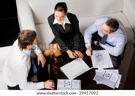 Three business partners sitting around table and planning work at briefing - stock photo