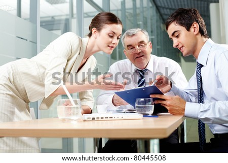 Three business partners sitting in office and sharing their ideas - stock photo