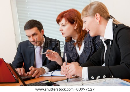 Three business people are meeting in the office